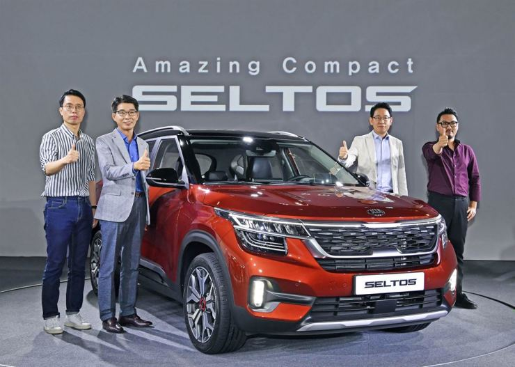 Kia Motors Vice President Kwon Hyuk-ho, second from left, and officials at the carmaker pose with the Seltos during the vehicle's launching ceremony in Yeoju, Gyeonggi Province, Thursday. The compact SUV comes with both 1.6-liter petrol and diesel powertrains, and the price starts at 19.29 million won. Courtesy of Kia Motors