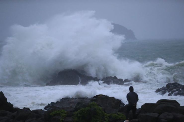 A man watches waves battering the coast of Jeju Island, Saturday, as Typhoon Danas hit the island. Yonhap