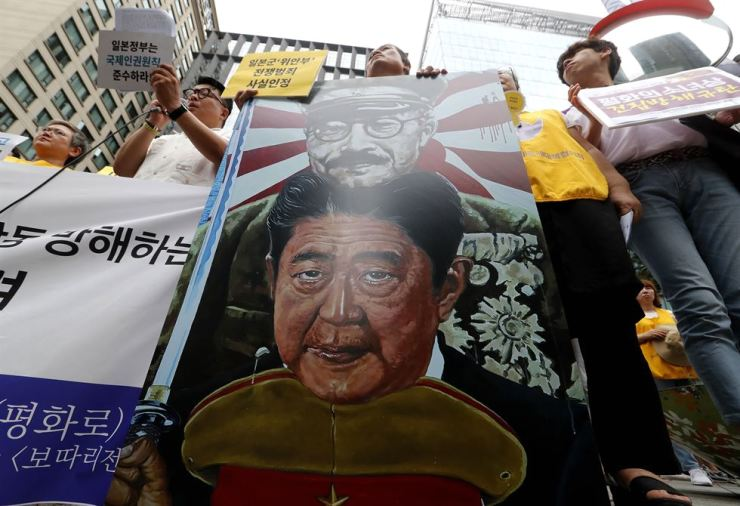 Protesters with an image of Japanese Prime Minister Shinzo Abe, bottom, stage a rally denouncing the Japanese government's decision on curbing their exports to South Korea in front of the Japanese Embassy in Seoul, July 24. Colonial-era Korean forced laborers recently launched a legal step to get court approval for the sale of local assets of their former Japanese employer Mitsubishi Heavy Industries, which has refused to compensate the former workers. AP-Yonhap