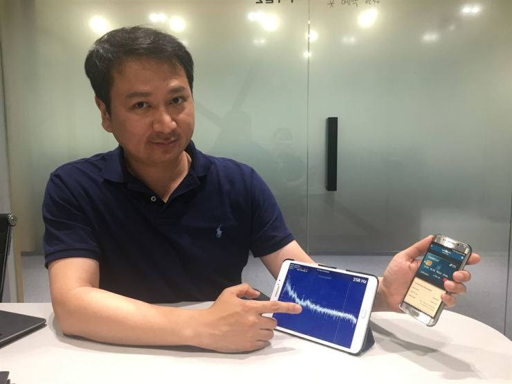 Infosonic CEO Cho Hoon-taek demonstrates how the company's proximity data transmission technology using inaudible sound works, at Woori Bank's Dinno Lab in Yeouido, Seoul, May 29.  Korea Times photo by Kim Bo-eun