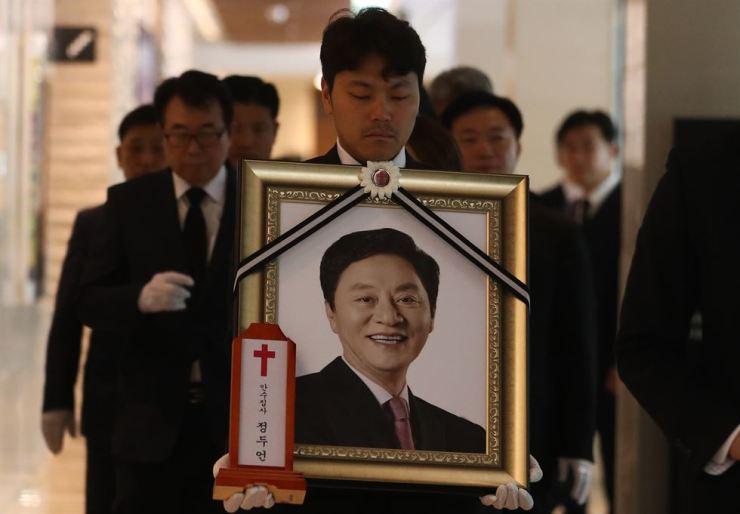 A man carries a framed photo of the deceased politician Chung Doo-un during his funeral at Yonsei University Severance Hospital in western Seoul on Friday. Chung was found dead last Tuesday on a western section of Mount Bukhan in Seoul. / Yonhap