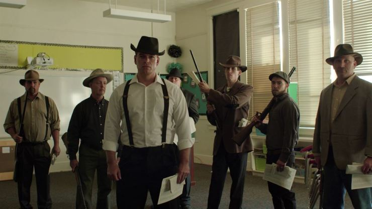This undated photo provided by 4th Row Films, town residents dressed in period costume stand in a modern day classroom in 'Bisbee '17,' as they re-enact the deputizing of a private police force that broke up a brewing strike at a copper mine on July 12, 1917, when they rounded up some 1,200 miners, locked them into cattle cars and deported them over the state line into a barren part of southern New Mexico. The dark history of Bisbee was largely an open secret for decades in the funky old copper town just seven miles north of the U.S.-Mexico border. AP