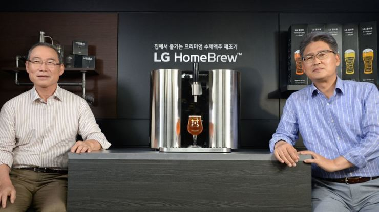 Song Dae-hyun, left, president of the home appliance & air solutions division at LG Electronics, and Kim Jung-tae, head of the firm's B2C group, pose with the HomeBrew beer-making machine during a press conference at the British Embassy in Seoul, Tuesday. / Courtesy of LG Electronics