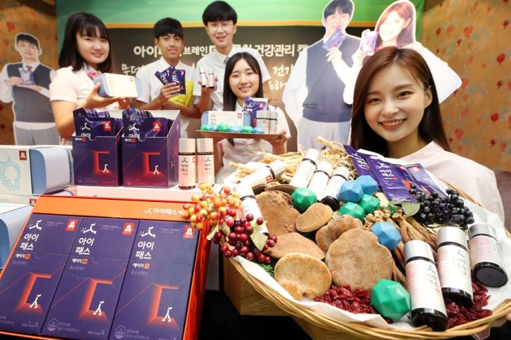 Students and a model display Cheong Kwan Jang's student tonic 'I-pass Brain,' at Korea House in Seoul, Monday. The ginseng company said the product helps boost the immune system and improve memory. Yonhap