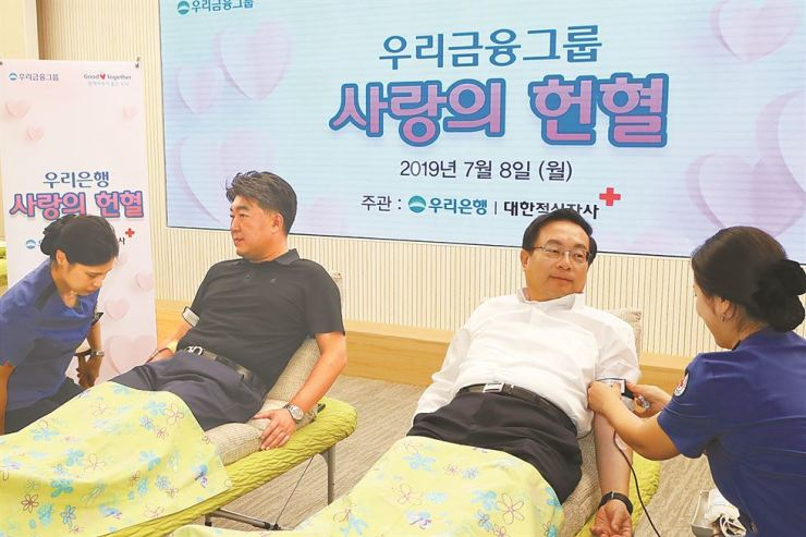 Woori Financial Group Chairman Sohn Tae-seung, second from right, donates blood with employees at the bank's headquarters in central Seoul, Monday. Woori has conducted a blood donation campaign every summer, since 2006 when it signed an agreement with the Korean Red Cross. / Courtesy of Woori Financial Group