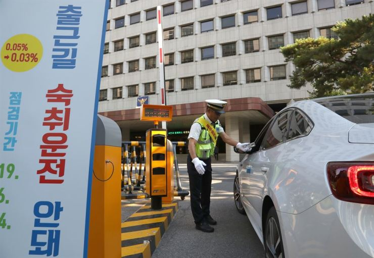 A police officer conducts a sobriety test on a driver arriving at work at Seoul Metropolitan Police Agency on the morning of June 24, a day before tougher drunk driving regulations took effect, in an effort to deter people from driving in the morning following a night of binge drinking. / Yonhap