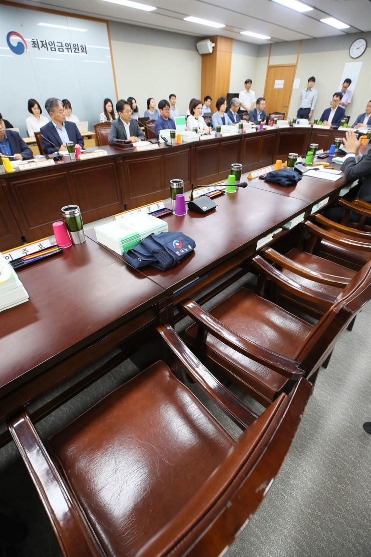 Seats reserved for labor representatives remain empty at the Minimum Wage Commission meeting in Sejong Government Complex, Tuesday. Labor representatives boycotted the meeting in protest of the business sector's proposal to cut the minimum wage from 8,350 won ($7.07) to 8,000 won next year. The labor sector has demanded the minimum wage be raised to 10,000 won, one of President Moon Jae-in's election promises. / Yonhap