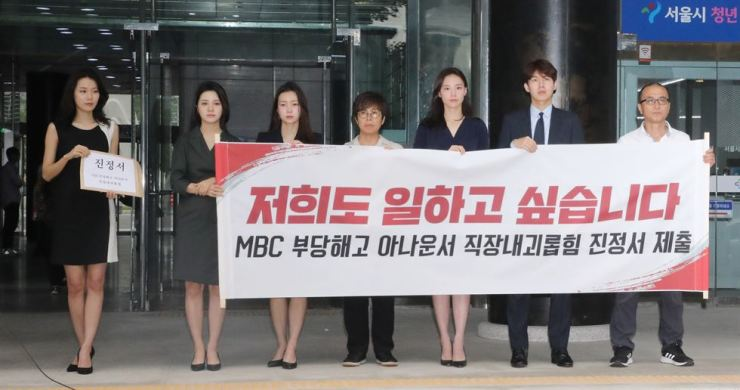 Announcers of local broadcaster MBC hold a press conference in front of the Seoul Labor Office, Tuesday, claiming the company was violating the law against workplace bullying that took effect the same day. / Yonhap