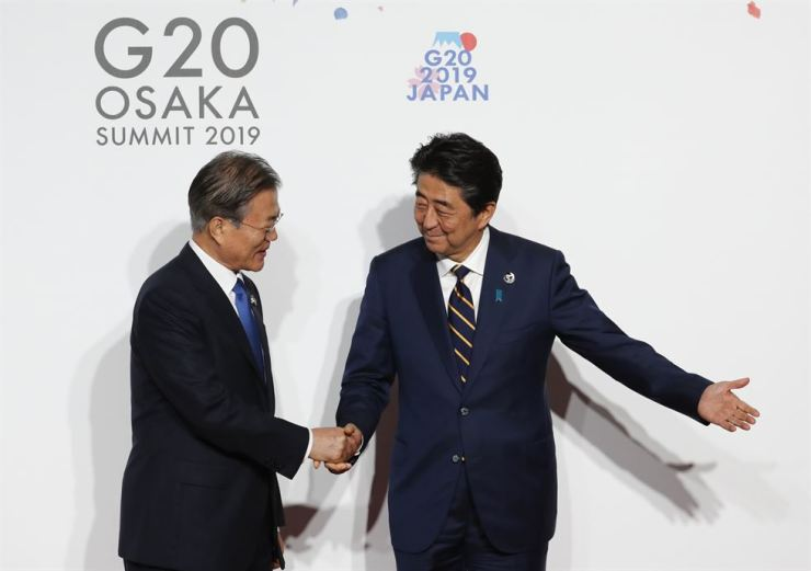 President Moon Jae-in, left, is welcomed by Japanese Prime Minister Shinzo Abe upon his arrival for an welcome and family photo session at G-20 leaders summit in Osaka, Japan, June 28. AP