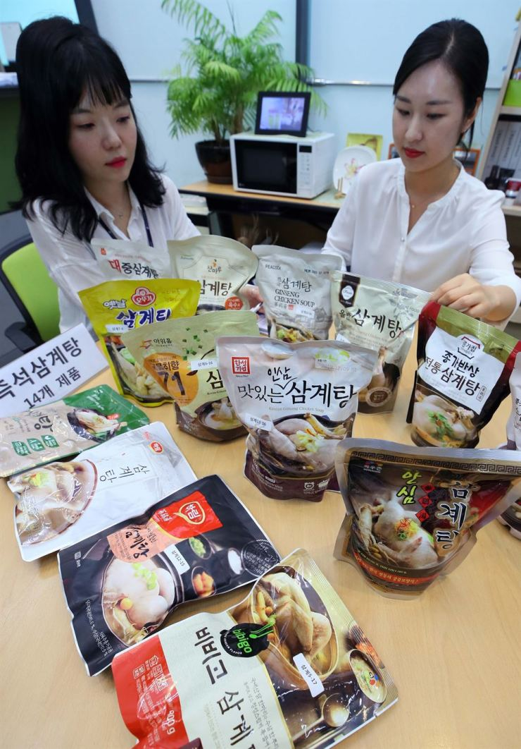 Staffers of the Korea Consumer Agency show packed samgyetang (chicken ginseng soup) products at the Government Complex Sejong, Thursday. The agency examined 14 precooked samgyetang products and found they contain a high level of sodium, 75 percent of the recommended daily consumption level per pack on average. /Yonhap