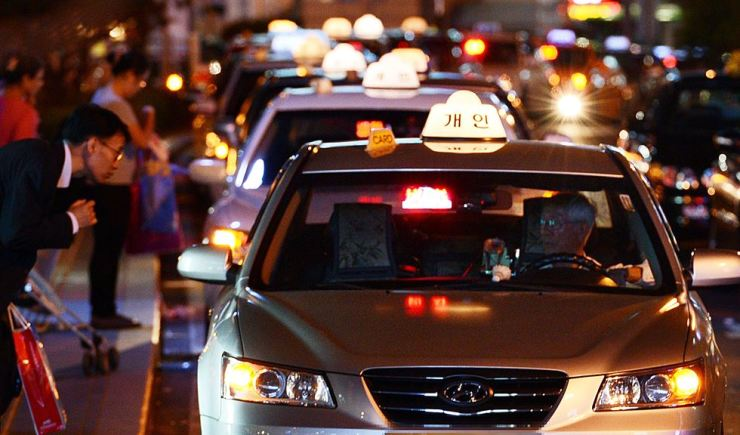 Citizens try to catch taxis at Seoul Station, central Seoul. / Korea Times file
