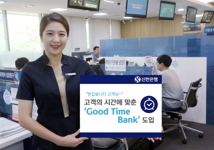 A model holds a banner promoting Shinhan Bank's flexible business hour system at the bank's head branch in central Seoul, Tuesday. / Courtesy of Shinhan Bank