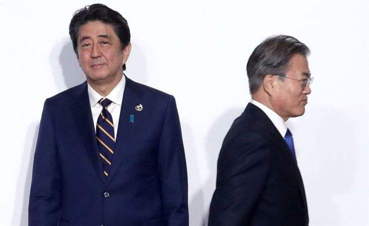 President Moon Jae-in moves along after shaking hands with Japanese Prime Minister Shinzo Abe during the G20 meeting in Osaka, Japan, on June 28. Yonhap