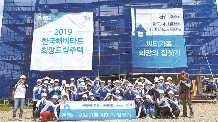 Citibank Korea workers pose during the bank's volunteer activity at a construction site in Cheonan, South Chungcheong Province, July 23. / Courtesy of Citibank Korea