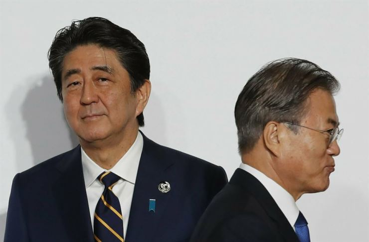 In this June 28 file photo, President Moon Jae-in, right, walks by Japanese Prime Minister Shinzo Abe upon his arrival for a welcome and family photo session at the G-20 leaders summit in Osaka, western Japan. The two major U.S. allies are again at odds, this time over Tokyo's decision to tighten controls on exports of sensitive materials that are mainly used in computer chips and display screens used in TVs and smartphones. The tensions reflect animosities that have persisted for decades. AP