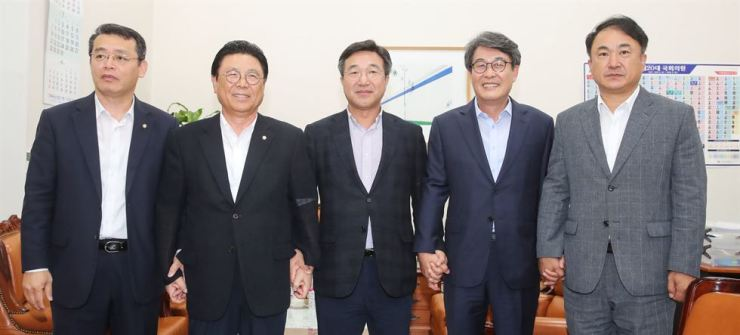 Secretary-generals of five political parties hold hands before their meeting at the National Assembly, Monday, on the establishment of a bipartisan body to win the ongoing trade war with Japan. From left are Rep. Lim Jae-hun of the minor opposition Bareunmirae Party, Rep. Park Maeng-woo of the main opposition Liberty Korea Party, Rep. Yun Ho-jung of the ruling Democratic Party of Korea, Rep. Kim Kwang-soo of the minor opposition Party for Democracy and Peace, and Kwon Tae-hong of the Justice Party. Yonhap