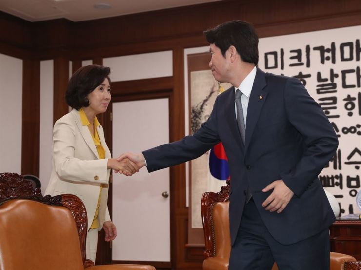 DPK floor leader Rep. Lee In-young, right, shakes hands with the main opposition Liberty Korea Party floor leader Rep. Na Kyung-won at the start of a meeting presided by National Assembly Speaker Moon Hee-sang for talks with the political parties following the introduction of Japan's export control measures, at the Assembly, Monday. Yonhap