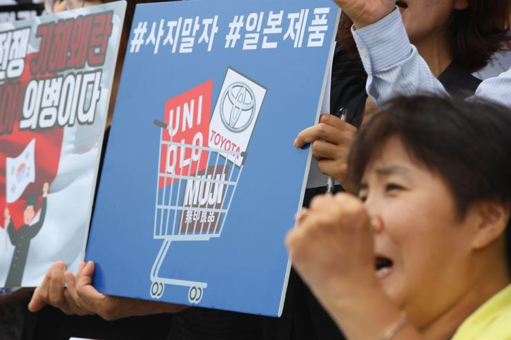 Civic group members hold banners urging consumers to join the boycott of Japanese products during a rally in front of a Uniqlo outlet in Sejong, Thursday. Yonhap