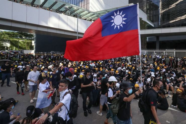 A protester holds Taiwan's national flag as he and other protesters gather outside the Legislative Council during the pro-democracy march in Hong Kong, July 1. EPA