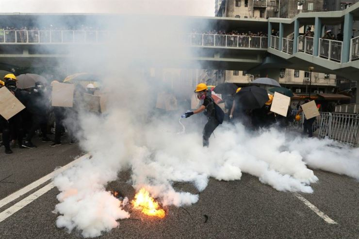 An anti-government protester tries to extinguish tear gas during a clash with riot police in Hong Kong, July 27. Photo from South China Morning Post