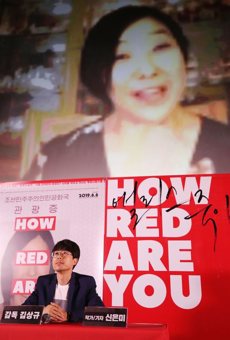Deported Korean American activist Shin Eun-mi is seen on a screen behind director Kim Sang-kyu who attends a news conference at a local theater in Seoul, Monday, to promote his documentary 'How Red Are You.' The film features Shin during her trip to South Korea in 2014 when she was on a book tour and claimed North Korea is a welfare state where human rights are protected. Shin was deported to the United States in 2015 and received a five-year travel ban to South Korea. The documentary film will hit local theaters on Aug. 8. / Yonhap