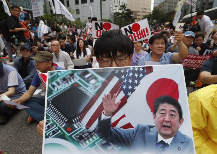 A protester holds a banner showing an image of Japanese Prime Minister Shinzo Abe during a rally denouncing the Japanese government's decision on their exports to Korea in front of the Japanese embassy in Seoul, July 20. AP