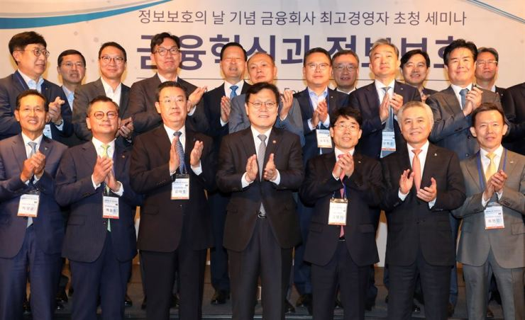 Financial Services Commission Chairman Choi Jong-ku, front row center, and CEOs of financial firms applaud during a seminar at Four Seasons Seoul, Wednesday, to celebrate Information Security Day. Choi urged the CEOs to prioritize financial stability and consumer protection for sustainable financial innovation. / Yonhap