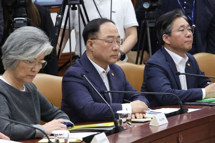 Deputy Prime Minister Hong Nam-ki, center, closes his eyes during a ministerial meeting over Japan's export restrictions at the Government Complex in Seoul, Thursday. From left are Foreign Minister Kang Kyung-wha, Hong and Industry Minister Sung Yun-mo. Yonhap