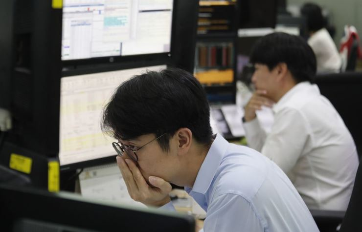 A currency trader watches monitors at the foreign exchange dealing room of the KEB Hana Bank headquarters in Seoul, Monday. AP