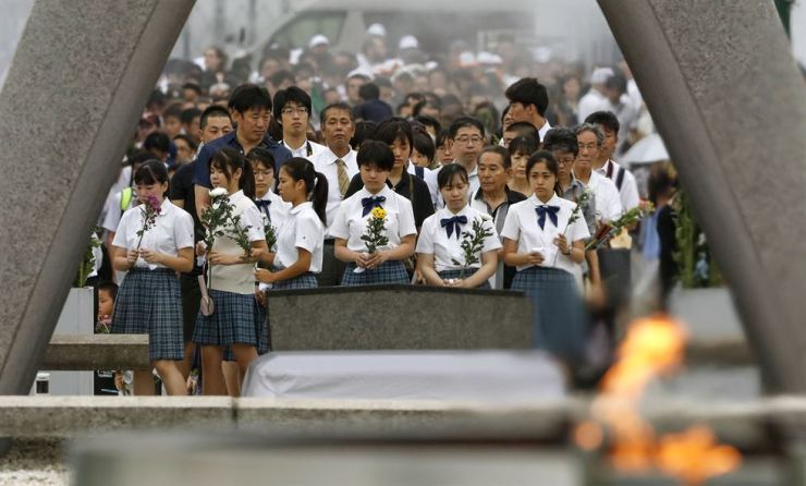 People pray for the atomic bomb victims in front of the cenotaph at the Hiroshima Peace Memorial Park in Hiroshima, western Japan during a ceremony to mark the 74th anniversary of the bombing Aug. 6. AP