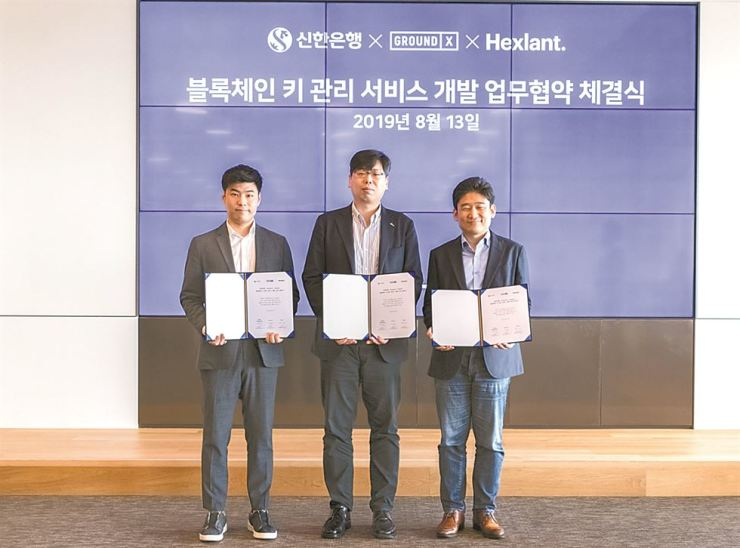 Shinhan Bank Digital R&D Center head Jang Hyun-ki, center, holds an MOU with Ground X CEO Han Jae-sun, right, and Hexlant CEO Noh Jin-woo at the Ground X head office in Seoul, Tuesday. / Courtesy of Shinhan Bank