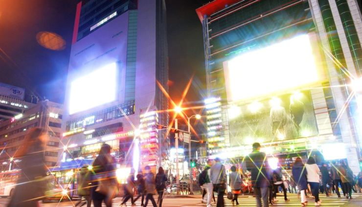 People cross the road near Gangnam Station in Seoul, where LED lights for outdoor advertising signs light up the district as if it were daytime. The threat of light pollution continues to grow as the demand for artificial lighting increases. Korea Times file