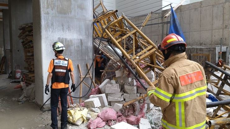 Rescue workers search the wreckage of a crashed elevator in an apartment construction site in Sokcho, Gangwon Province, Wednesday. Yonhap