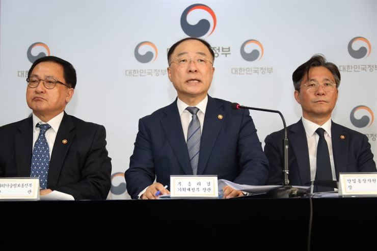 Deputy Prime Minister Hong Nam-ki, center, speaks during a press conference at the Government Complex in Seoul, Friday. Hong said Korea will remove Japan from its whitelist of countries with preferential trade status, in response to Tokyo's decision to exclude Seoul from its whitelist earlier Friday. Yonhap