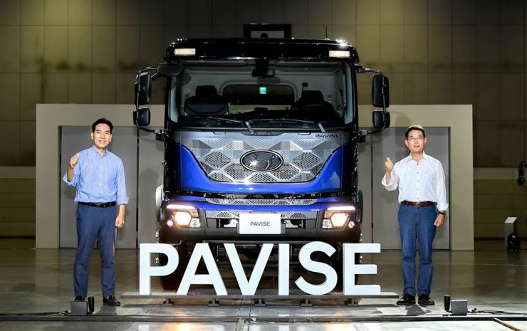 Hyundai Motor Executive Vice President Lee In-cheol, right, and Senior Vice President Lim Chung-hwan poses with the Pavise truck during the carmaker's truck and bus business fair at KINTEX in Goyang, Gyeonggi Province, Thursday. Courtesy of Hyundai Motor