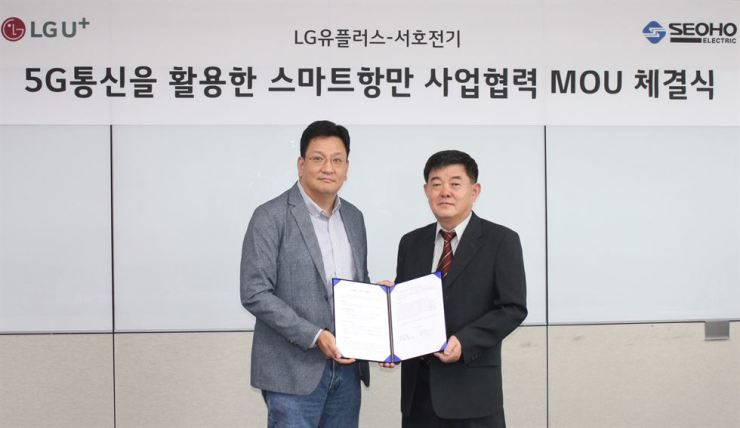 Suh Jae-yong, left, a vice president who heads the Enterprise 5G Business Unit at LG Uplus, poses for a photo with Seoho Electric CEO Kim Seong-nam at the mobile carrier's head office in central Seoul, Wednesday, after signing an MOU to cooperate in constructing a 'smart' port system. / Courtesy of LG Uplus