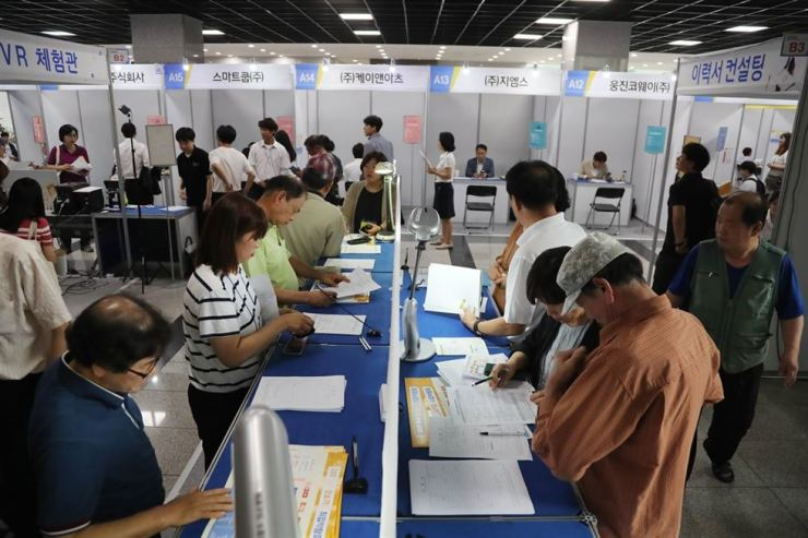 People fill out application forms for job interviews at a job fair in Seoul in this June photo. A job fair for Japanese companies, which was planned to be held in the second half of the year, has been canceled amid chilled relations between Korea and Japan following the latter's trade restrictions. / Yonhap