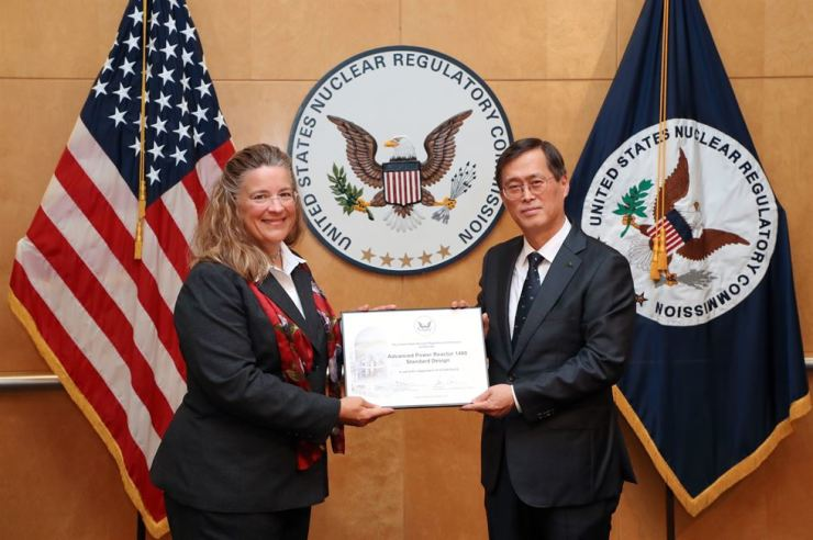 Korea Hydro & Nuclear Power CEO Chung Jae-hoon holds a design certification for its APR1400 light water reactor with U.S. Nuclear Regulatory Commission Commissioner Annie Caputo in Washington D.C., Monday (local time). With the design certification, U.S. power generators can build and operate the APR1400 without a standard design approval review. It is the first non-U.S.-made reactor to earn such certification. Courtesy of Korea Hydro & Nuclear Power
