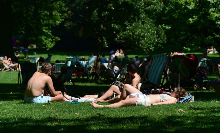 People sunbathe at Saint James Park in London. Many vacationers suffer from sunburns after their summer vacation, and doctors advise soothing the skin with a cold, wet towel. Korea Times file