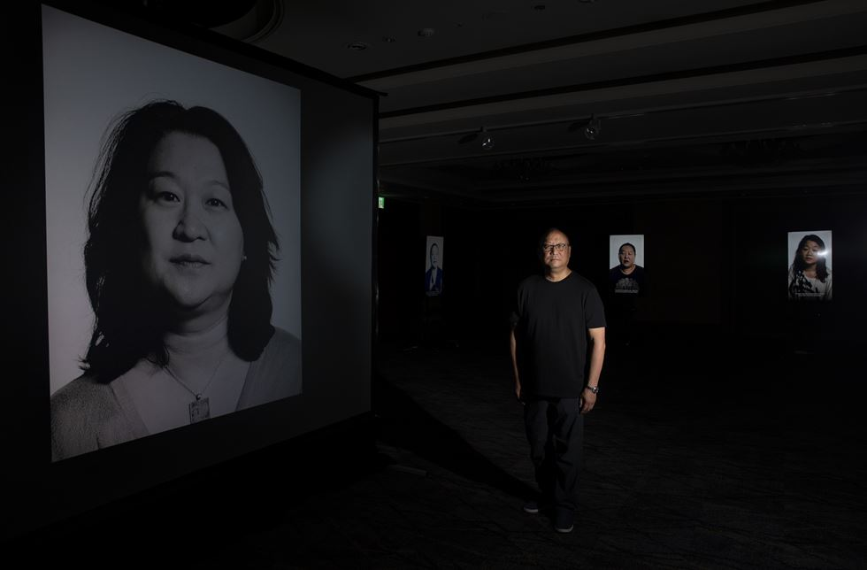 Filmmaker Glenn Morey stands by the window at the entrance to his video art exhibit for his film 'Side by Side: Out of a South Korean Orphanage and into the World' at Lotte Hotel Seoul, Wednesday. / Korea Times photo by Shim Hyun-chul