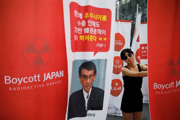 A protester at an anti-Japan rally stands next to a banner mocking the Japanese Foreign Minister Taro Kono's promotional remarks on Fukushima's food safety. Reuters-Yonhap