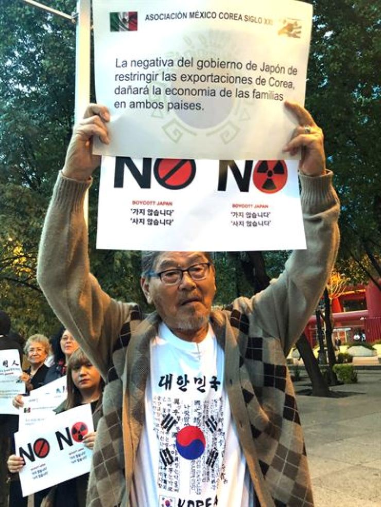 A Korean descendant in Mexico holds a sign to protest Japan's export restrictions on Korea during a rally in Mexico City, Wednesday. / Yonhap