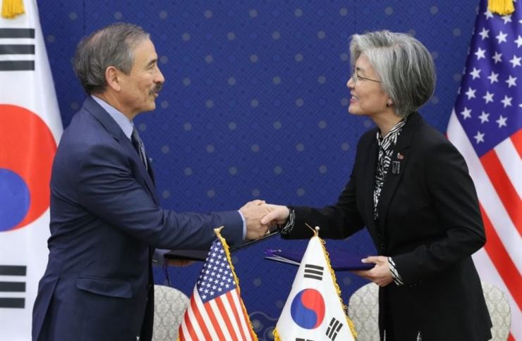 Foreign Minister Kang Kyung-wha shakes hands with U.S. Ambassador to South Korea Harry Harris after they sign the 10th Special Measures Agreement, or the latest defense cost sharing agreement, at the former's headquarters in Seoul on March 8. Yonhap