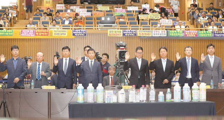 Key witnesses in the scandal involving deadly humidifier disinfectants, including senior officials of the product manufacturers and researchers, take an oath during a fact-finding hearing by the Special Investigation Commission on Social Disasters, at Seoul City Hall, Tuesday. The deadly products claimed over 1,400 lives, and the commission is seeking ways to support the victims. / Yonhap