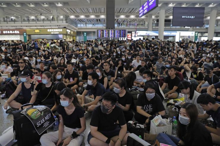 Thousands take part in a second day of sit-in protest at the airport in Hong Kong on Saturday, Aug. 10, 2019. Hong Kong is in its ninth week of demonstrations that began in response to a proposed extradition law but have expanded to include other grievances and demands for more democratic freedoms. AP