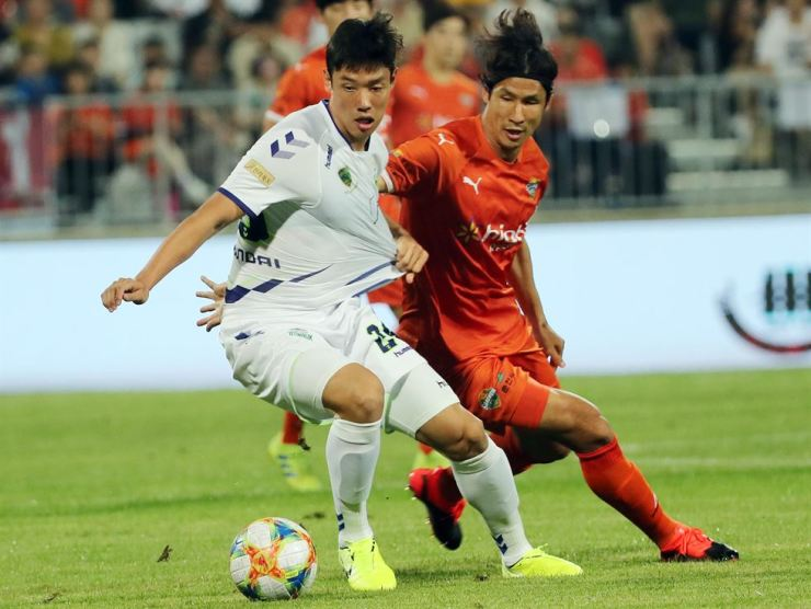 Hong Jeong-ho of Jeonbuk Hyundai Motors, left, vies for the ball with Jung Jo-gook of Gangwon FC during a 2019 Hana1Q K League match at Songam Sports Town in Chuncheon, Gangwon Province on Aug. 4. Yonhap