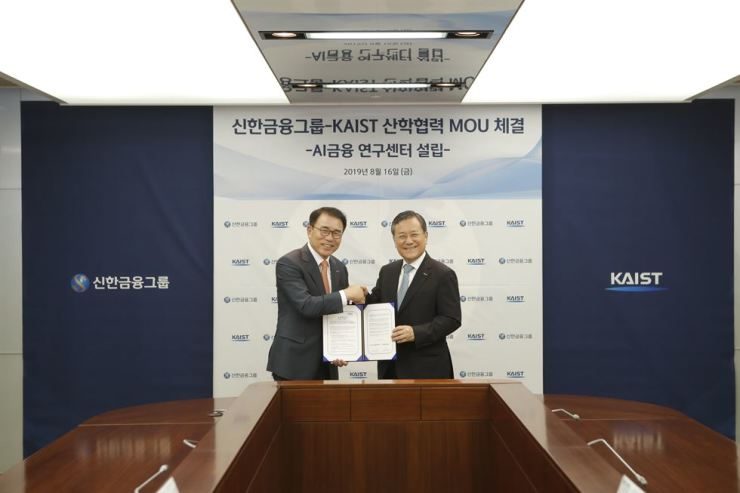 Shinhan Financial Group Chairman Cho Yong-byoung, left, and Korea Advanced Institute of Science and Technology (KAIST) President Shin Sung-chul shake hands while holding a signed memorandum at the bank's headquarters in Seoul, Aug. 16. The two agreed to boost cooperation in joint research concerning artificial intelligence-related financial algorithms. Courtesy of Shinhan Financial Group