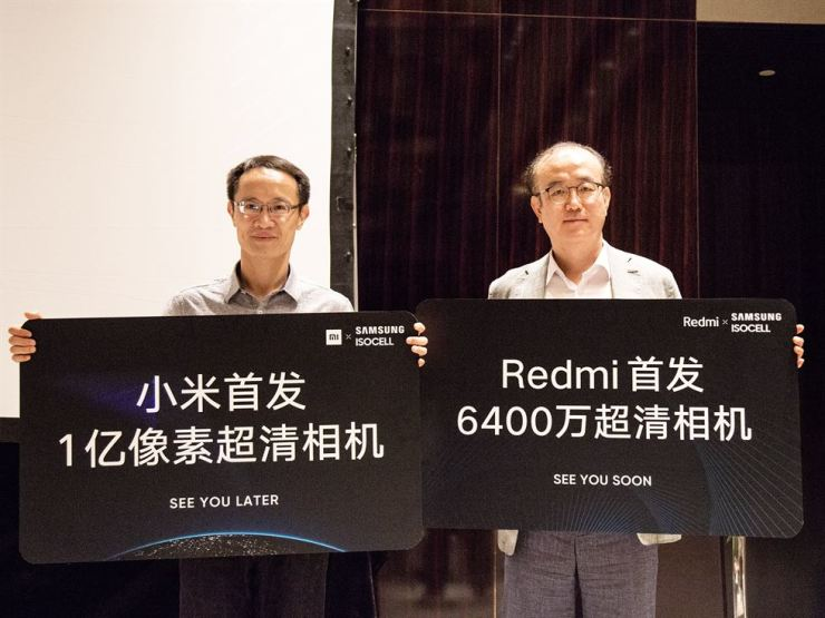 Lin Bin, left, co-founder and president of Xiaomi, with Lee Je-suk, vice president of Samsung Electronics, during an event in Beijing Wednesday to unveil Xiaomi's new smartphone that uses Samsung's 64-megapixel image sensor. / Courtesy of Xiaomi