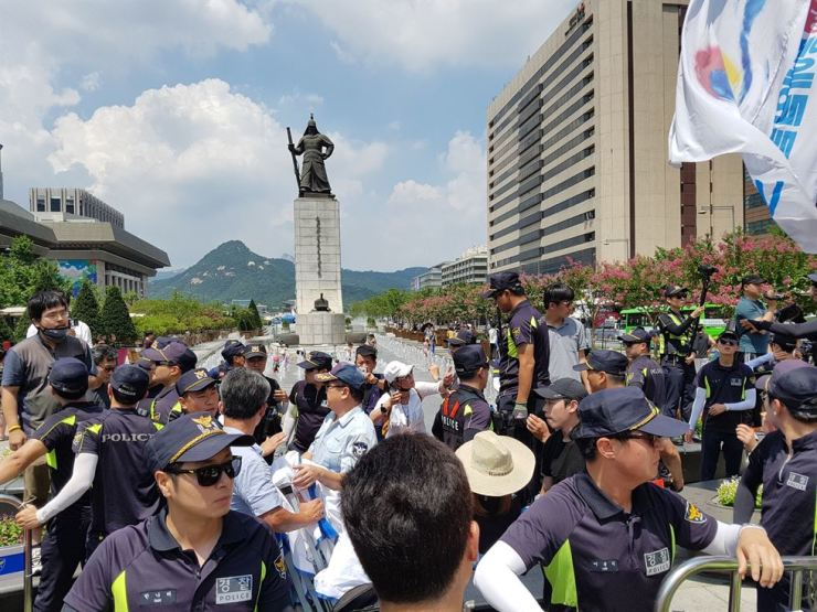 Police try to keep the peace among liberal and conservative protesters to prevent their potential clash at Gwanghwamun Square, central Seoul, Aug. 3. /Courtesy of Richard Pennington