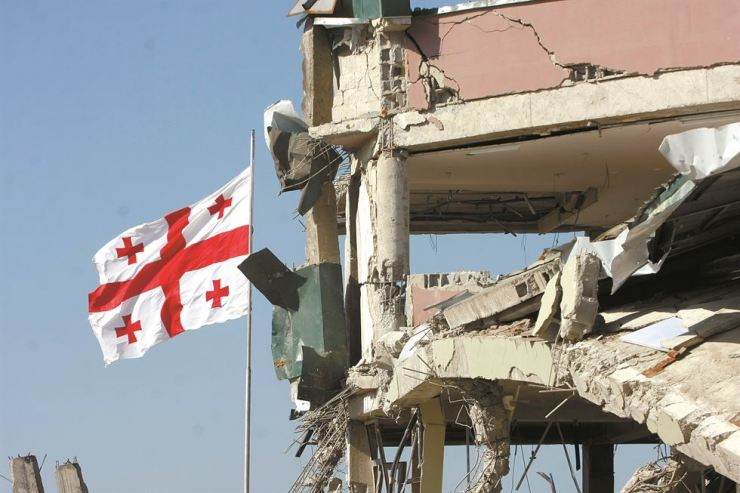 A Georgian flag flies by a demolished building during the Russian-Georgian War in Abkhazia and Tskhinvali/ South Ossetia from Aug. 7-12, 2008. / Embassy of Georgia